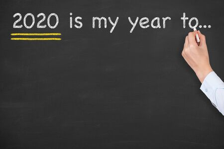 Human Hand Writing 2020's my year to ... on Blackboard Background Archivio Fotografico