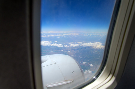 Airplane window with a view of sky and clouds  photo