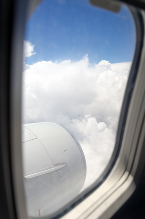 Airplane window with a view of sky and clouds. photo