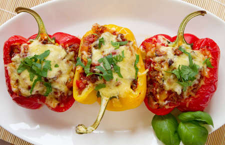 Baked stuffed red bell pepper filled with minced meat, onion, rice, tomato and green onion  Stock Photo