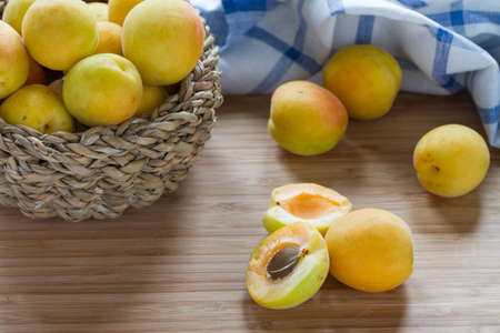 Apricots in wicker basket on wooden table