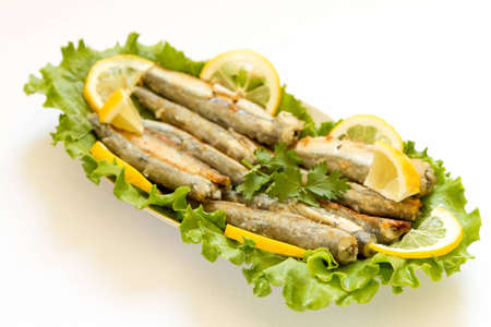 Grilled Capelin, on leaves of salad on a white background photo