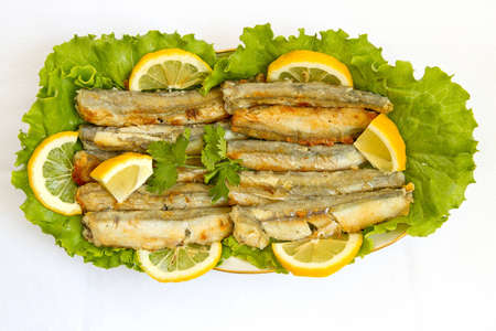 Grilled Capelin, on leaves of salad on a white background, top view  photo