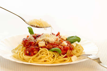 Spaghetti Bolognese and Parmesan cheese on spoon Stock Photo