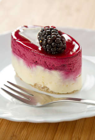 Blackberry fruit Tart on a white plate with a fork photo
