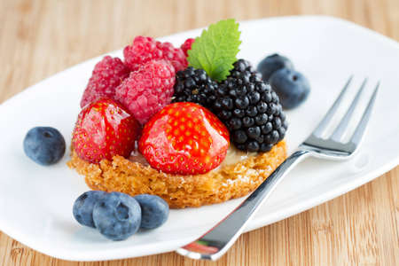 fruit cake with berries on white plate with a fork