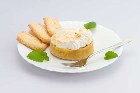 fresh lemon tart witht hree biscuits on white plate with a fork  photo