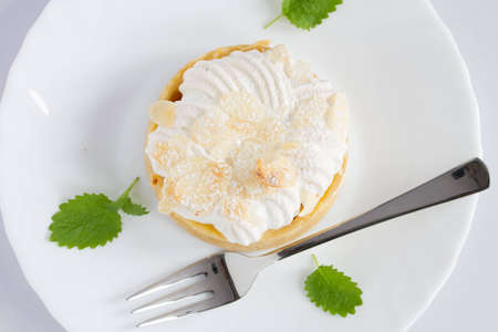 lemon tart on white plate with a fork, top view photo