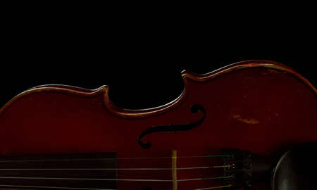 Old scratched violin isolated on black photo