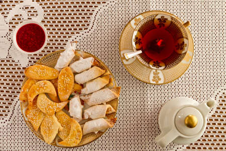 Heap of cookies with fruit jam and cup of tee, top view