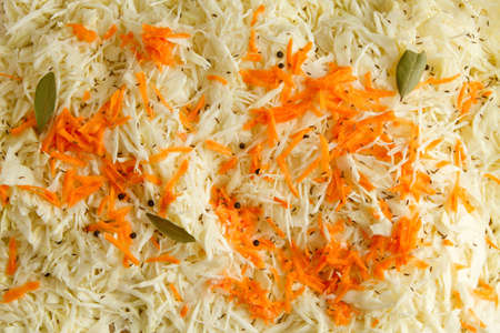 Close-up of a cut cabbage with carrots and peppers and lavrov  1110;m leafs, top view  Stock Photo