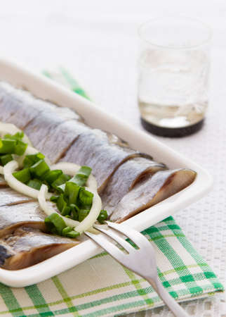 Portion of herring fillets with herbs on the plate Stock Photo