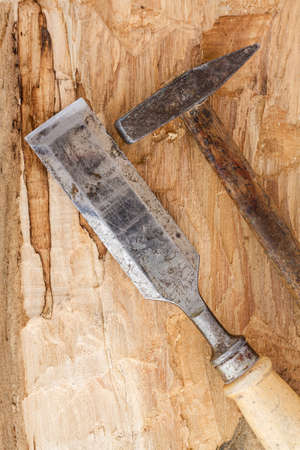 Old used hammer and chisel on wood background  Stock Photo