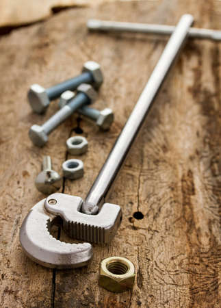 Chrome wrench and set of nuts bolts on wood background