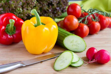 Cut vegetables, salad ingredients on wood board