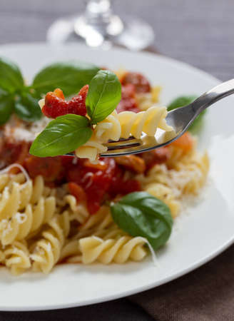 Fusilli pasta with sauce bolognese hanging on a fork