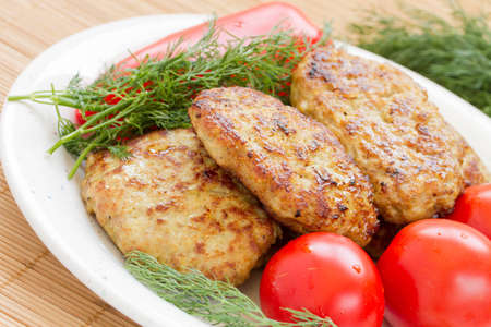 Fried meatballs with dill and tomatoes on a plate  Stock Photo