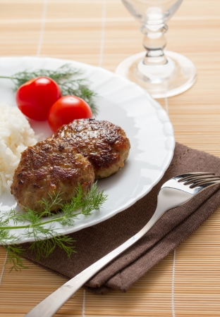 Meatballs with rice, dill and tomatoes served on white plate photo