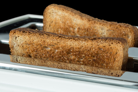 Closeup of toasted bread and toaster on black background Stock Photo