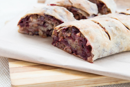 plate: Apple strudel with cherries and raisins on cutting board