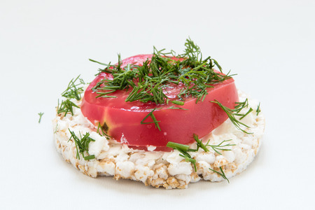 Round crisp breads with cheese, tomatoes and dill on a white background