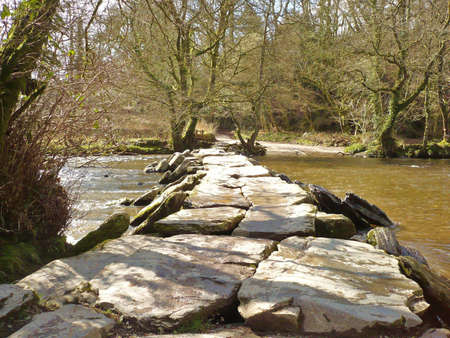 an ancient clapper bridge fording the River Barle, Exmoor, South West England.