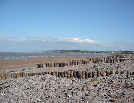 Groynes on a shingle and sandy beach with hills in the background