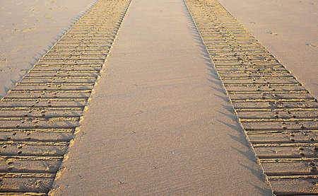Tyre tracks in the sand on a beach, South West England