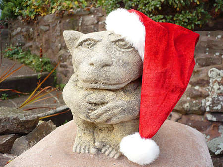 Garden statue with his Christmas hat on, South West England Stock Photo