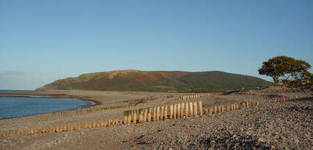 Shingle bank being eroded and breached at Porlock, and the bracken on the hillside looks crimson in Autumn, South West England Stock Photo