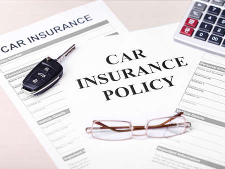 Car insurance policy. Document, key, glasses on table. Business and insurance background concept.