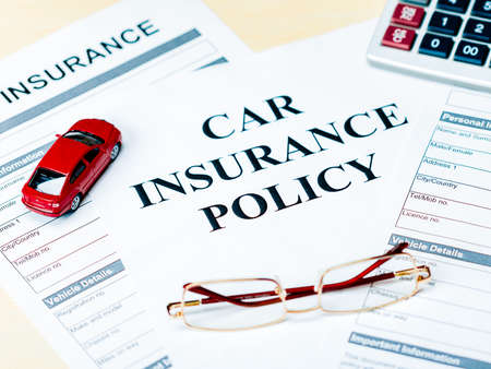 Car insurance policy. Document, model of car, glasses, calculator, pen and coins on table. Business and insurance background concept. Banque d'images