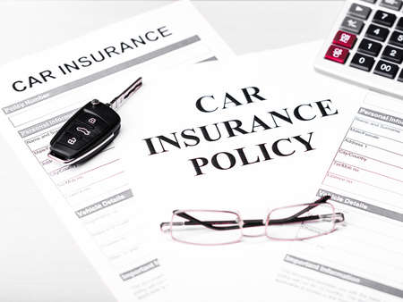 Car insurance policy. Document, car key, glasses and calculator on table. Business and insurance background concept.