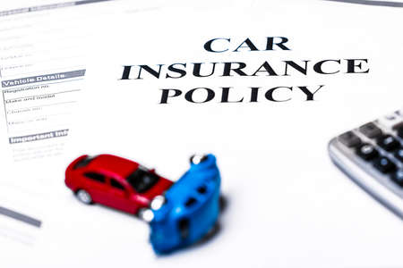Car insurance policy. Document, models of cars and calculator on table. Business and insurance background concept.