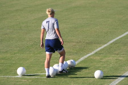 soccer kicker lining up balls for practice