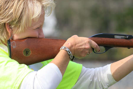Lady rifle competitor aiming at a target