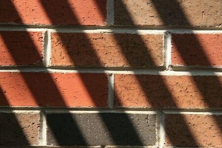 Angled shadows on a brickwall Stok Fotoğraf