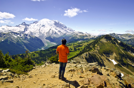 A man watching Mt Rainier from top of a Trail