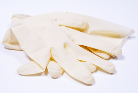 surgical cap: Surgical latex glove and cap on white background.