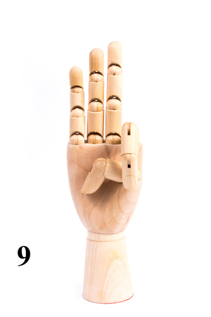 Sing of number nine from wooden hand isolated on white background Stock Photo