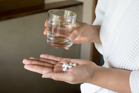 Female hands hold medicine tablet and glass. Healthcare concept. Stock Photo