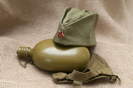Army water bottle and cap with a star on the background fabric.