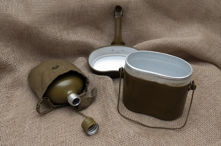 Army water bottle and bowler on the background fabric. Stock Photo