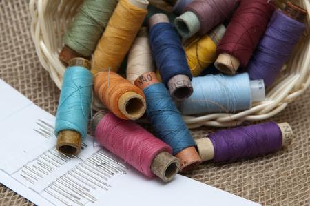 basket embroidery: Handicraft supplies in basket on burlap background
