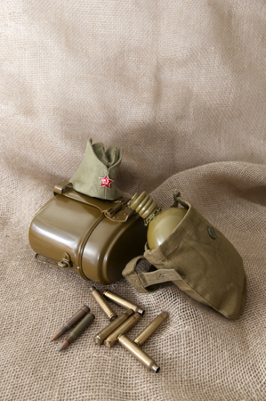 rudely: Army water bottle cap with a star, cartridges on the background fabric. Stock Photo