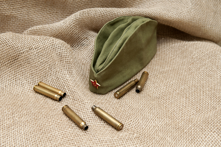 Army cap with a star and cartridges on the background fabric.