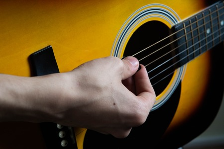 Hand of man playing six string guitar Reklamní fotografie