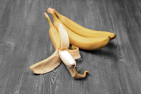 three fresh bananas on wooden background