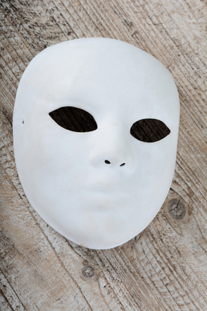White mask on the brown vintage wooden table background