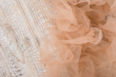 Lightweight fabric mesh lace on textured wooden table, texture of the fabric is beautifully draped background